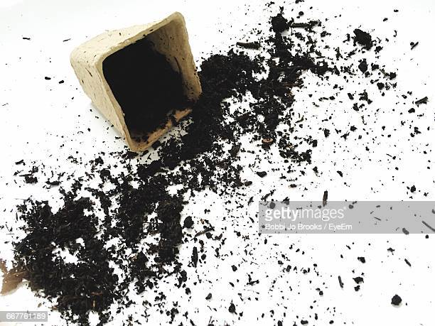 High Angle View Of Dirt With Broken Container On White Background