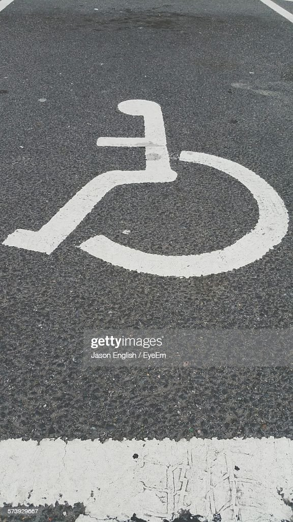 High Angle View Of Disabled Sign On Road At Parking Lot