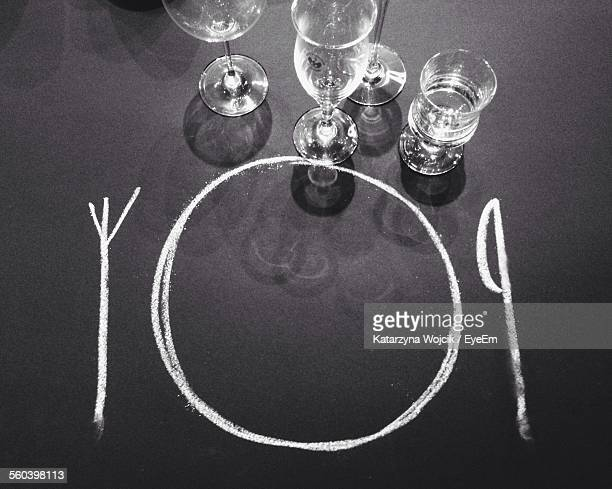 High Angle View Of Drawing And Wine Glasses On Table