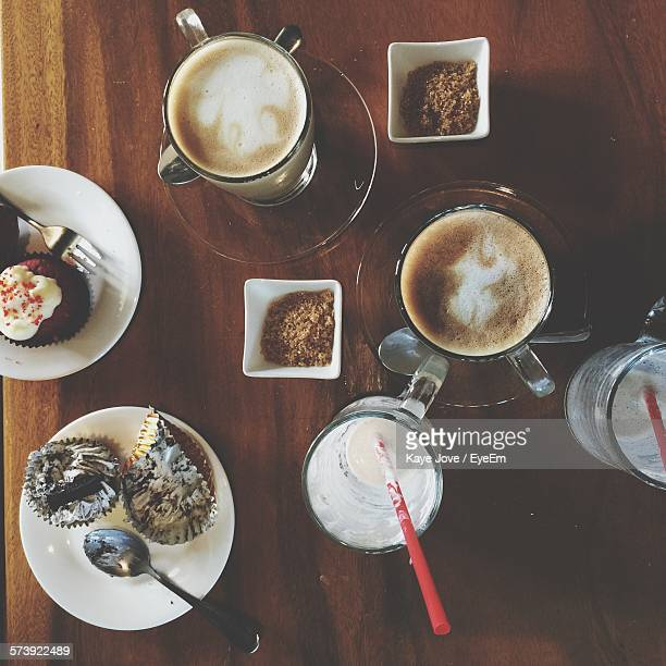 High Angle View Of Drink And Cupcakes On Table