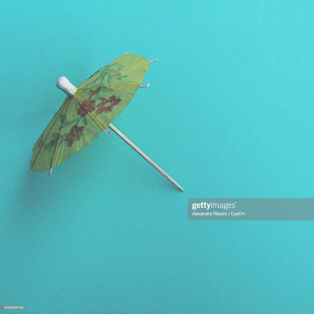 High Angle View Of Drink Umbrella Against Turquoise Background