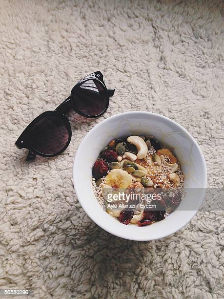 High Angle View Of Dry Fruits In Bowl By Sunglasses On Carpet