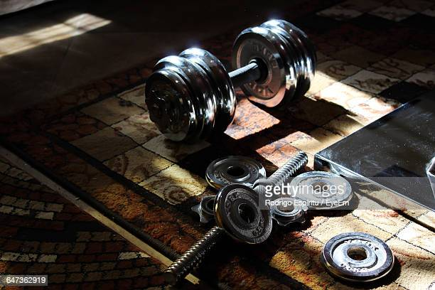 High Angle View Of Dumbbell And Barbell On Carpet
