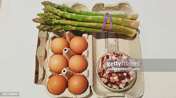 High Angle View Of Eggs And Meat With Asparagus Carton