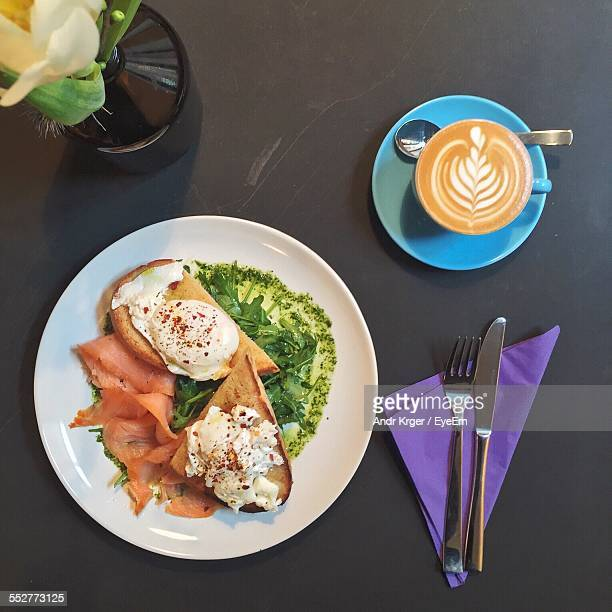 High Angle View Of Eggs Benedict And Coffee Served On Table