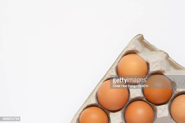 High Angle View Of Eggs In Carton On White Background