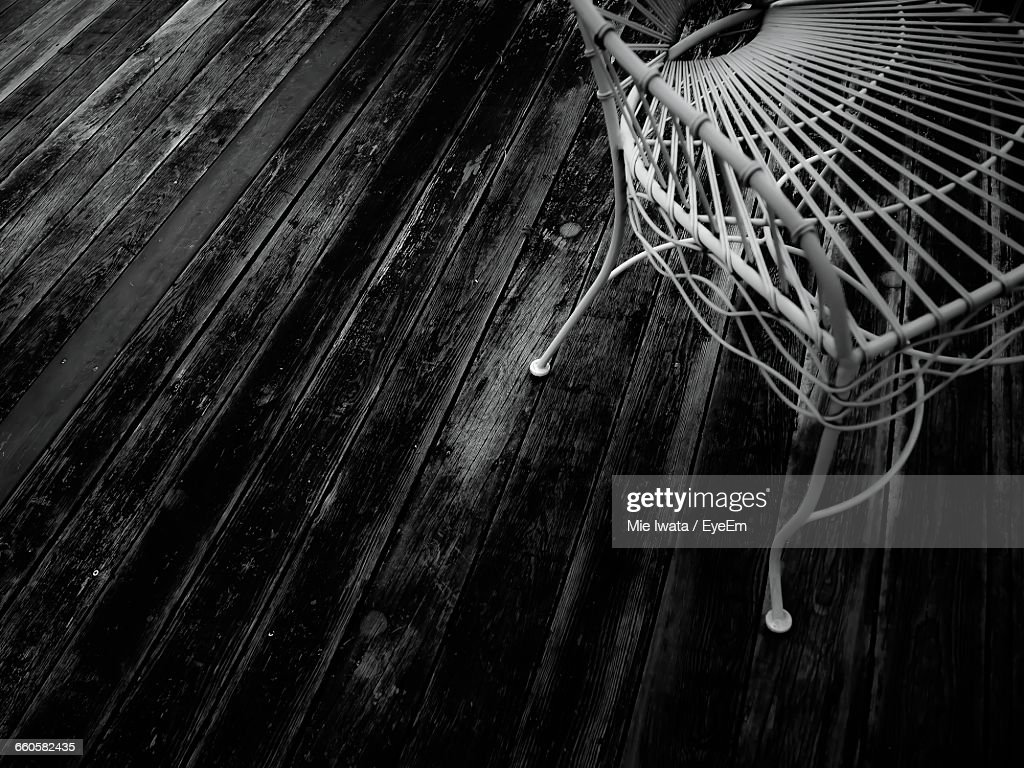 High Angle View Of Empty Chair On Boardwalk In Back Yard