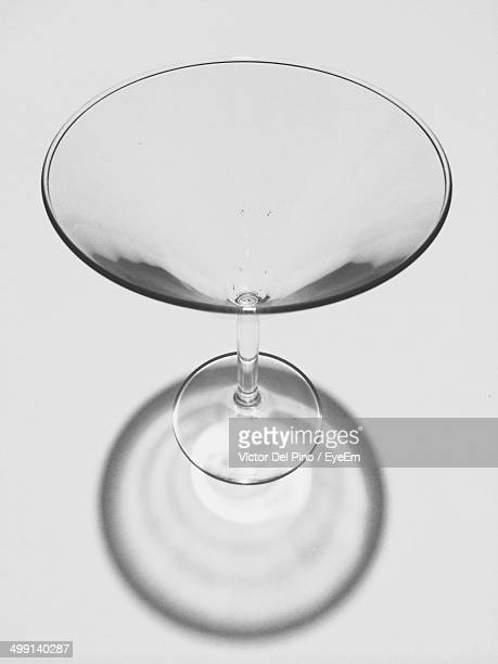 High angle view of empty martini glass over gray background