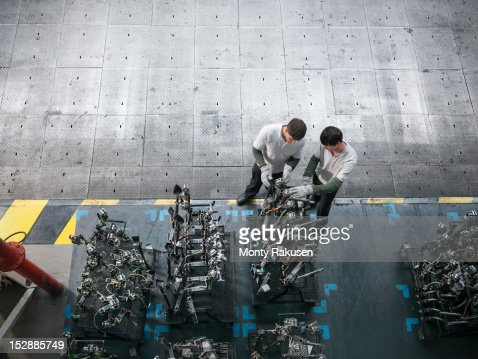 High angle view of engineers inspecting press parts in car factory