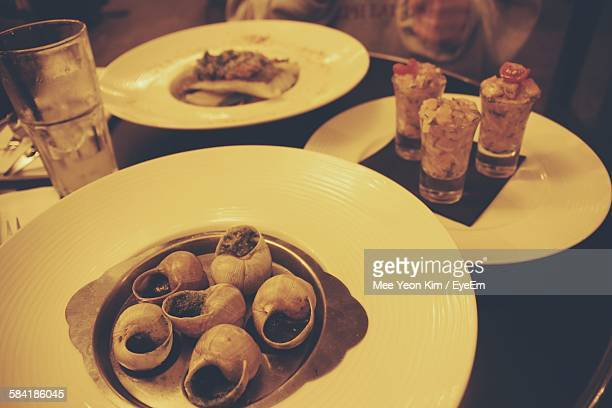 High Angle View Of Escargots With Tartare Served On Table