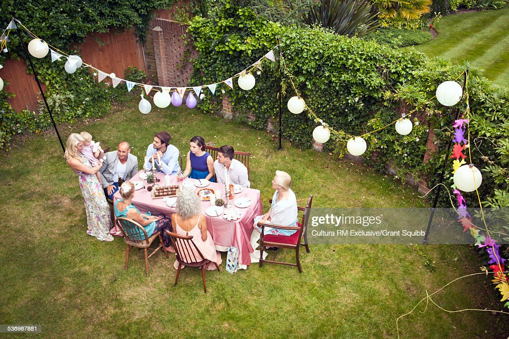 High angle view of family and friends around table at garden party