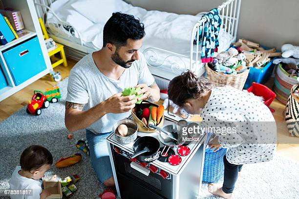 High angle view of father and children playing with toy kitchen in bedroom at home