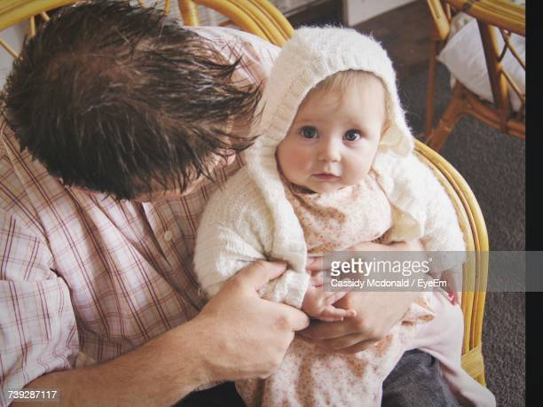 High Angle View Of Father Carrying Cute Daughter On Lap