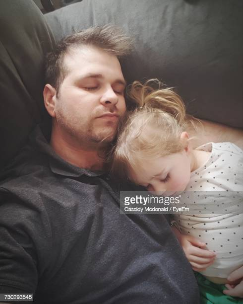 High Angle View Of Father With Daughter Sleeping On Sofa