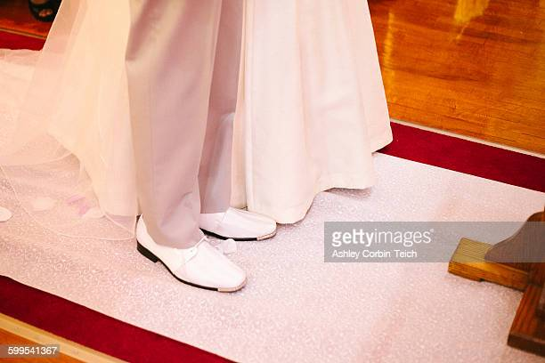 High angle view of feet of bride and bridegroom standing together in church