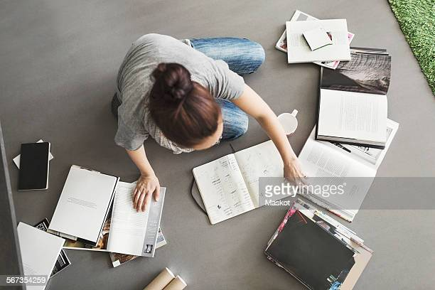 High angle view of female architect working on floor at home office