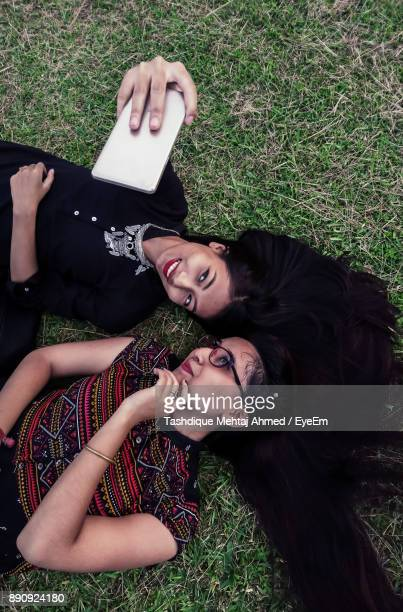 High Angle View Of Female Friends Taking Selfie While Lying On Grass