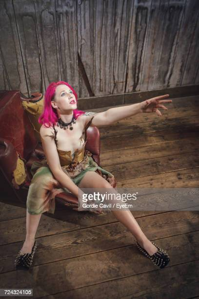 High Angle View Of Female Model Looking Up While Sitting At Chair On Hardwood Floor
