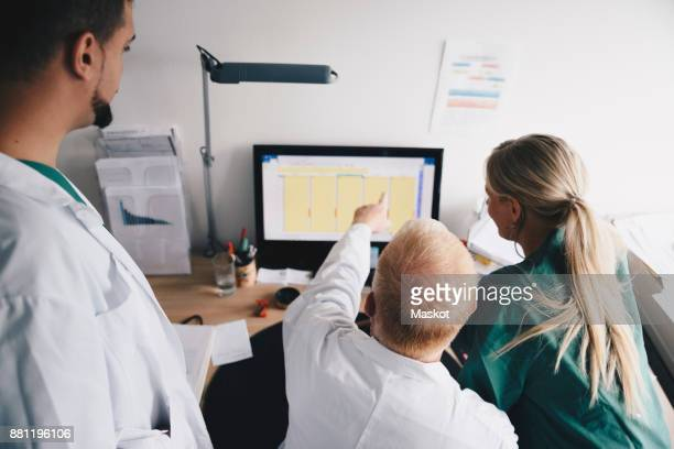 High angle view of female nurse and male doctors discussing over computer at office