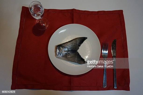 High Angle View Of Fish Tail Served In Plate On Table