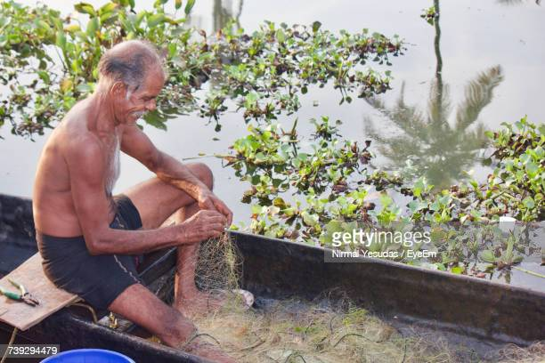 High Angle View Of Fisherman Weaving Net While Sitting On Boat By Lake