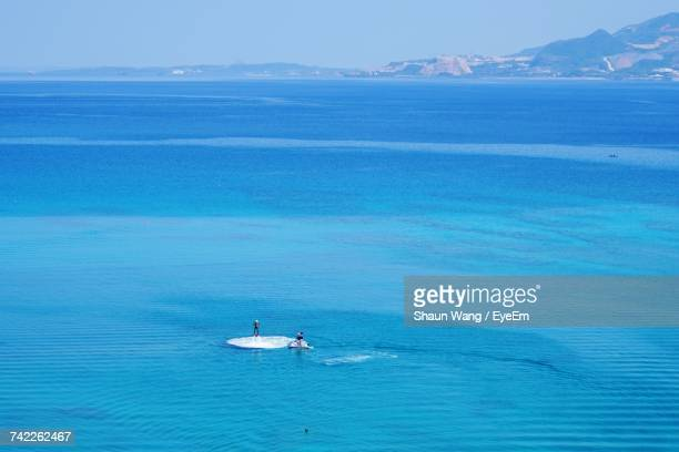 High Angle View Of Fly Boarder And Jet Skier In Blue Sea