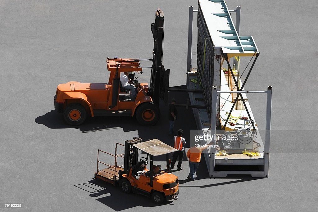 High angle view of forklifts and workers at a commercial dock : Foto de stock