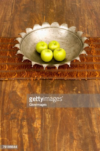 High angle view of four apples in a bowl at a dining table : Foto de stock