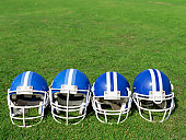 high angle view of four football helmets on a field