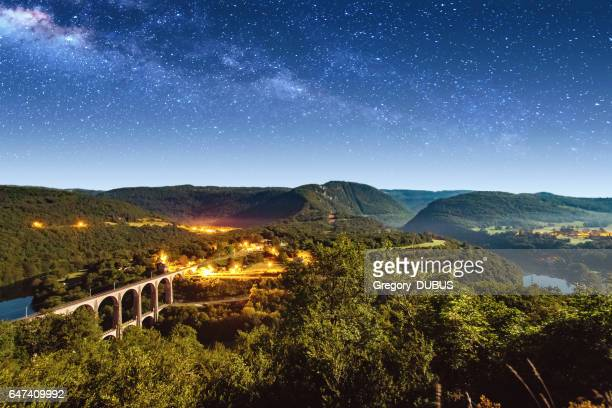 High angle view of french Bugey mountains beginning of Jura landscape by summer night with old stone railway viaduct arch bridge crossing Ain river and beautiful star sky
