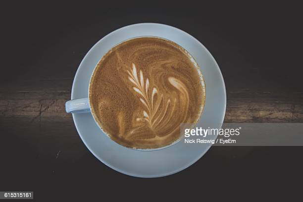High Angle View Of Fresh Coffee With Froth Art Served On Table
