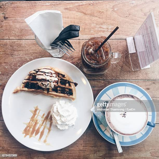 High Angle View Of Fresh Dessert Served With Coffee On Table
