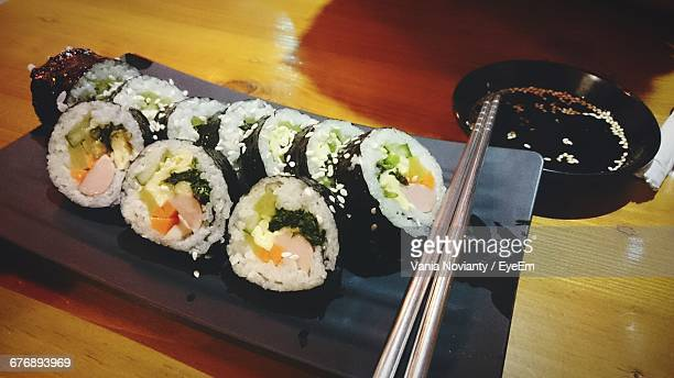 High Angle View Of Fresh Gimbap Served In Tray With Chopsticks On Table At Restaurant