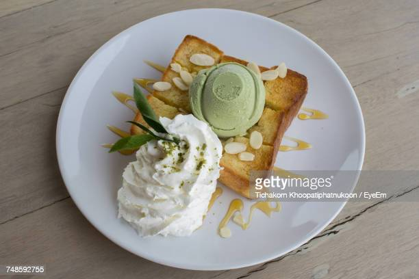 High Angle View Of Fresh Green Tea Ice Cream Served With Almonds And Whipped Cream On Toast In Plate