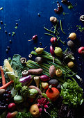 High angle view of fresh vegetables and fruits scattered on blue table