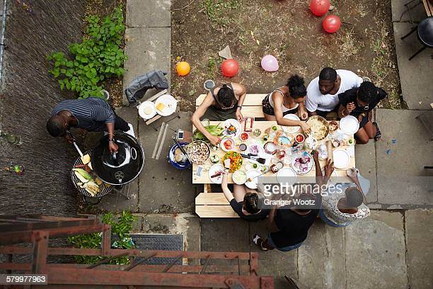 High angle view of friends enjoying backyard barbecue