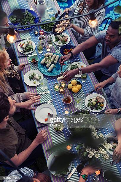 High angle view of friends having food at dining table in yard