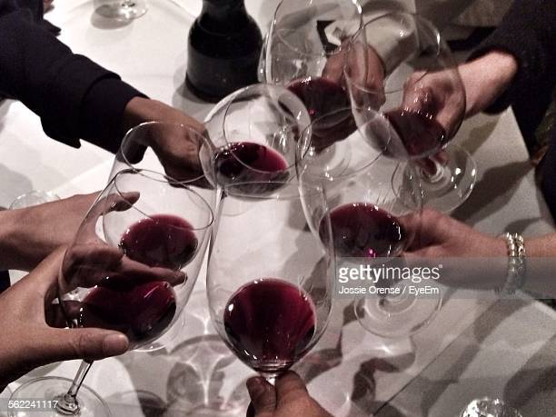 High Angle View Of Friends With Red Wine Toast On Table In Restaurant