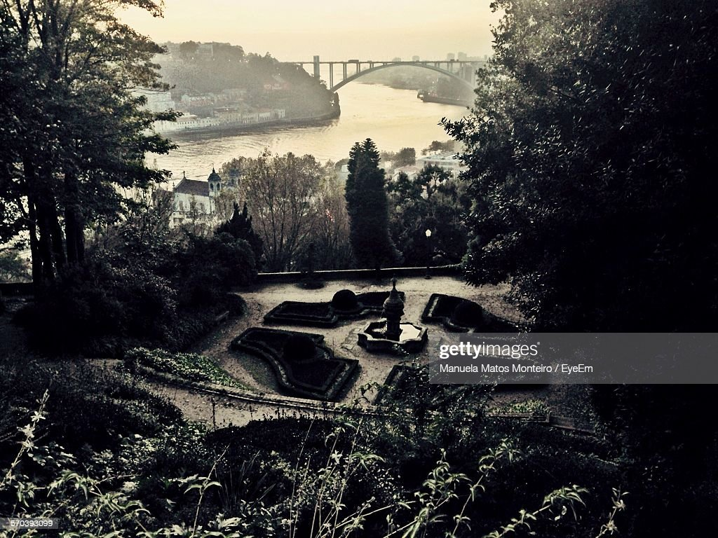 High Angle View Of Garden By Arch Bridge Over River Against Sky At Dusk