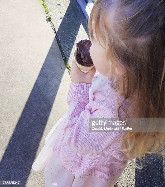 High Angle View Of Girl Eating Ice Cream While Standing On Footpath