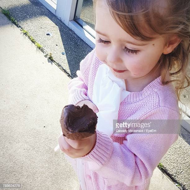High Angle View Of Girl Holding Ice Cream On Road