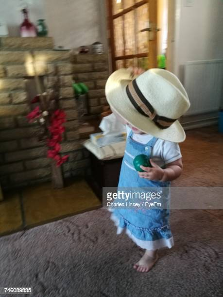 High Angle View Of Girl Holding Toy With Hat At Home