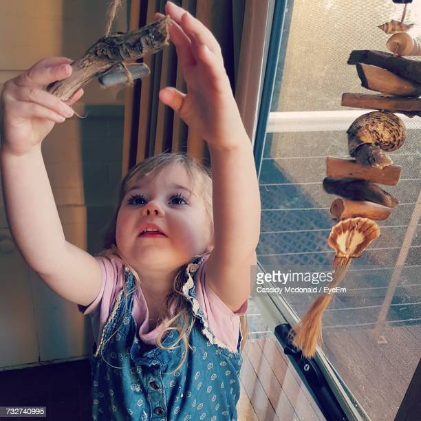 High Angle View Of Girl Holding Wind Chime Hanging By Glass Window