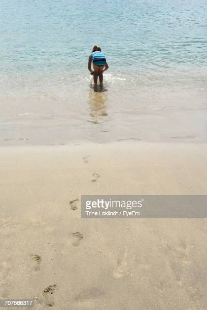 High Angle View Of Girl Playing On Sea Shore At Beach