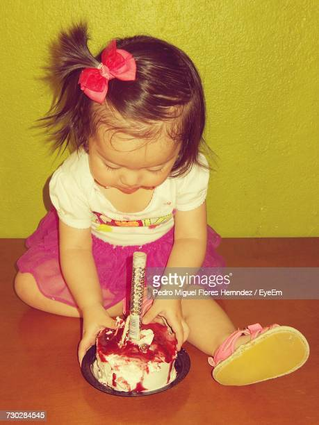 High Angle View Of Girl Sitting By Birthday Cake At Home