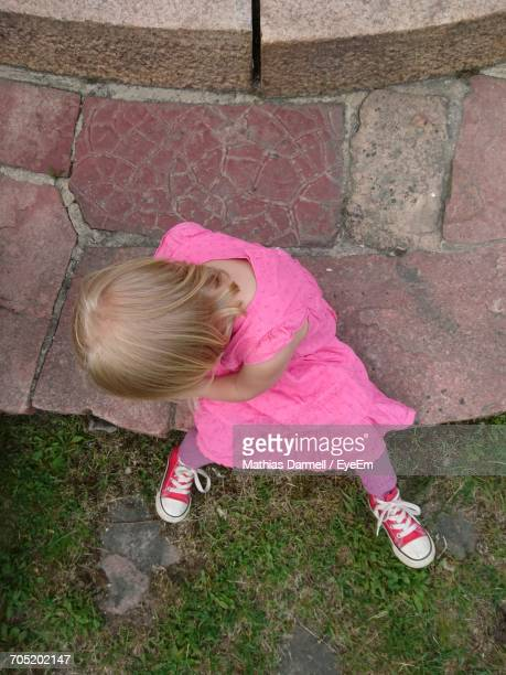 High Angle View Of Girl Sitting In Back Yard