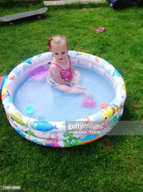 High Angle View Of Girl Sitting In Wading Pool At Yard