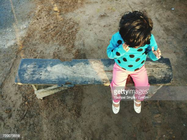 High Angle View Of Girl Sitting On Bench At Beach