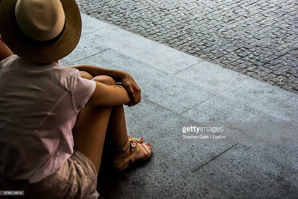 High Angle View Of Girl Sitting On Steps By Street