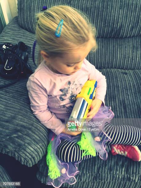 High Angle View Of Girl Sitting With Toy On Sofa
